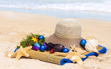beach mat: Christmas balls, hat, shells, sunglasses on the mat on the beach