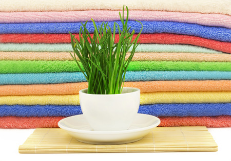 bathe mug: Spa concept with fresh grass with drops in the cup on the mat and multicolor towels Stock Photo