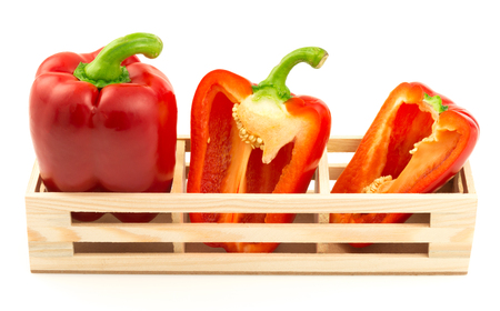 wooden basket: Group of sweet red peppers in the wooden box isolated on white background Stock Photo