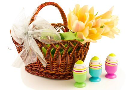 eggcup: Easter eggs, tulips in basket with bow isolated on white background