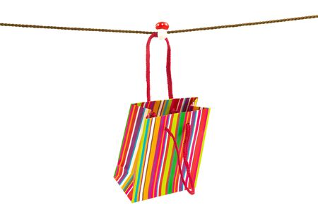 Colorful stripped shopping bag hanging on a rope isolated on white background