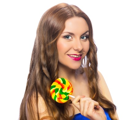 Beautiful playful girl holding a colorful twisted lollipop isolated on white background