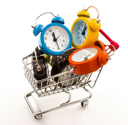 failed strategy: Color alarm clocks in the metal trolley isolated on white background Stock Photo