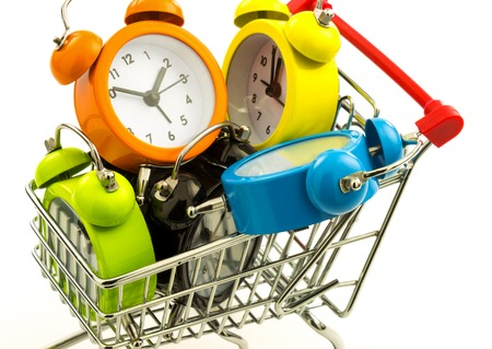 Macro view of color alarm clocks in the metal trolley isolated on white background