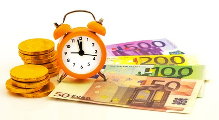 Alarm clock with paper euro money and gold coins isolated on white background Stock Photo