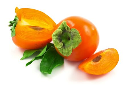 Macro view of ripe fresh persimmons with slices and bunch of green leaves isolated on white background