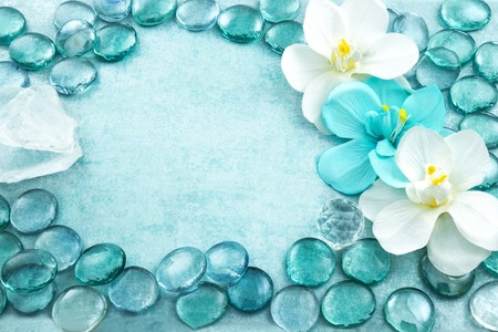 blue orchid: Macro view of blue glass drops with white flowers orchid and bar of sea salt, aqua background Stock Photo