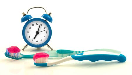 toothpaste: Composition from blue clock and toothbrushes with magenta toothpaste Stock Photo