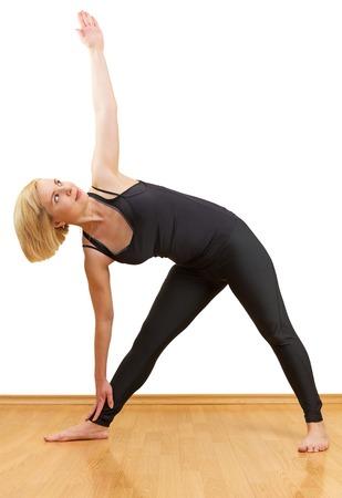 trikonasana: Blonde woman with short hair practicing yoga asana trikonasana exercise isolated on white background