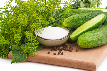 Macro view of cucumbers, bloom dill with black pepper on the wooden cutting board Reklamní fotografie
