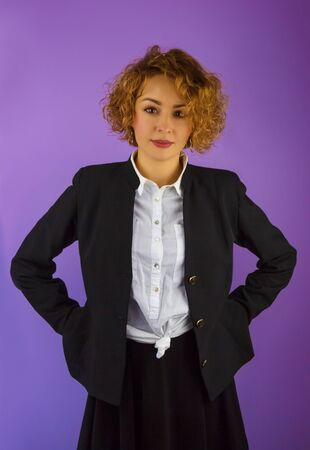 Attractive young woman with curly hair standing in a black suit on the violet background