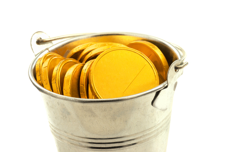 Macro view of metal bucket with gold coins isolated on white background Reklamní fotografie