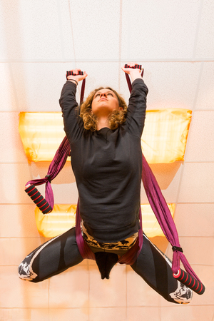 Woman making aerial yoga exercises with hammock under the ceiling
