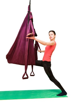 Woman making aerial yoga exercises with mat, fly yoga isolated on white background