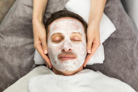 Face of man with cream mask and hands of professional cosmetologist, beauty, spa Reklamní fotografie