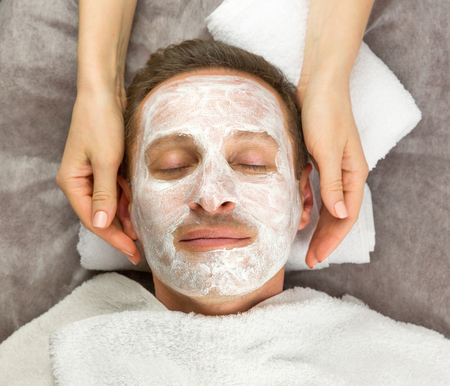 Face of man with cream mask and hands of beautician, beauty, spa Reklamní fotografie