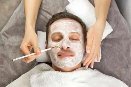 Face of man with cream mask, hands of beautician with brush, beauty, spa Reklamní fotografie - 62163451