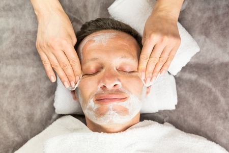 Macro view of smiling face of man with cream mask, towels, beauty, spa