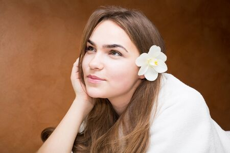 Smiling attractive young brunette woman in a white robe Reklamní fotografie