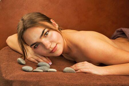 sauna nackt: Beautiful brunette woman with spa stones, indoor