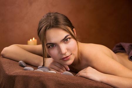sauna nackt: Attractive lying young woman in spa salon with stones and candles Lizenzfreie Bilder