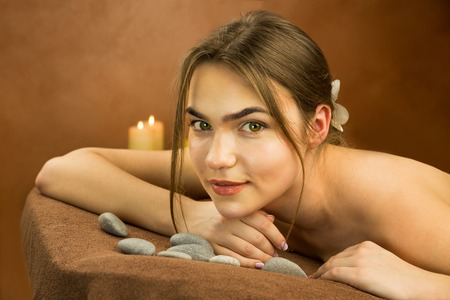 Attractive lying young woman in spa salon with stones and candles Standard-Bild