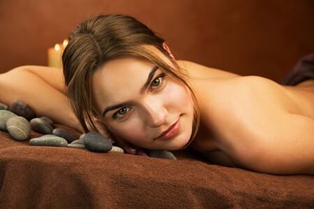 sauna nackt: Attraktive junge Frau auf einem Massagetisch liegend, close up