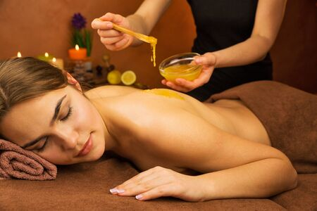Beautiful woman in spa salon having spa therapy honey procedure with hands of masseur Stock Photo