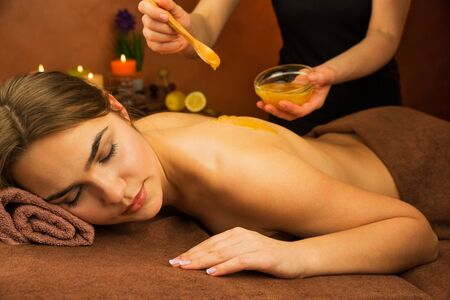 spa therapy: Beautiful woman in spa salon having spa therapy honey procedure with hands of masseur Stock Photo