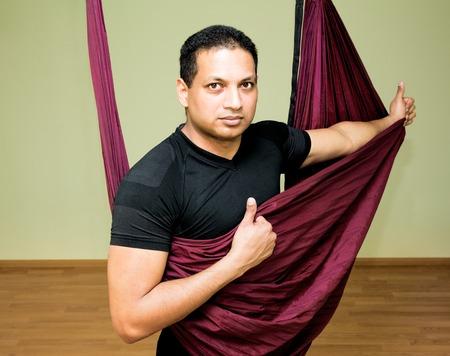 Man making aerial yoga exercises, indoor, aerial yoga Reklamní fotografie