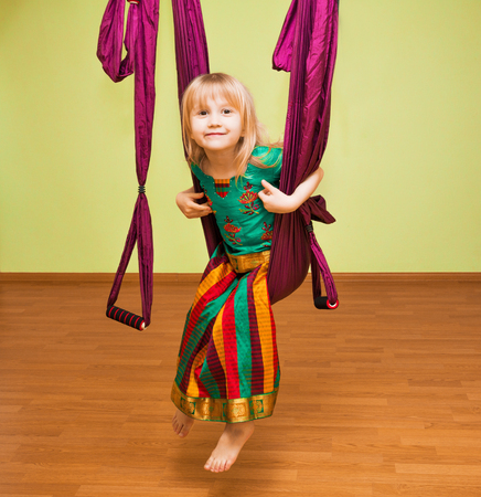 Little girl making aerial yoga exercises, indoor, fly yoga