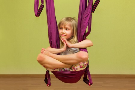 inversion: Little girl making aerial yoga exercises, indoor, fly yoga