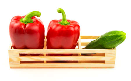 Group of sweet red peppers and fresh cucumber in the wooden box isolated on white background