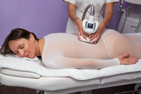 thinness: Woman in the white special suit having anti cellulite massage with apparatus