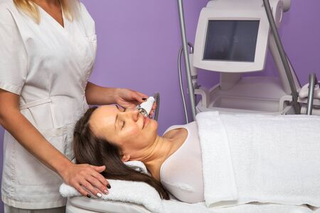 thinness: Woman having anti cellulite massage on her face with therapist and apparatus Stock Photo