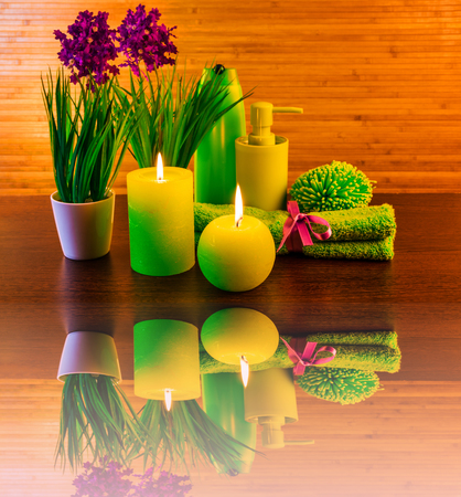 Green spa bath products concept with candles, flowers, towel with reflection Reklamní fotografie