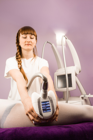A qualified therapist doing a anti cellulite massage with an apparatus in spa salon