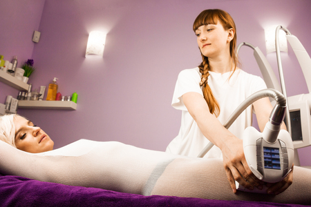 Woman having anti cellulite massage with therapist and apparatus Stock Photo