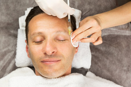 Face of happy laying man, hands of beautician with a syringe and sponge