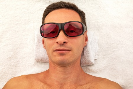 Relaxing handsome man with glasses in spa salon laying on white towel Reklamní fotografie
