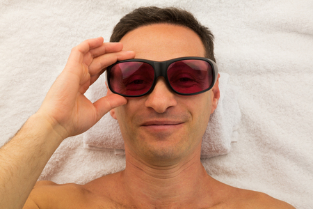 Relaxing handsome man with glasses in spa salon laying on white towel with hand