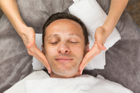Male face with cream mask, hands of professional beautician with white towel