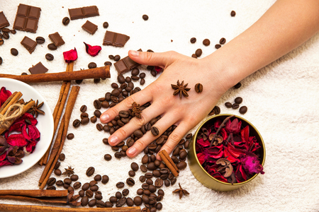 Spa composition with chocolate, coffee, red petals of rose flower and hands
