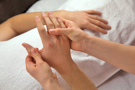 Hand massage with white towel, spa salon Stock Photo
