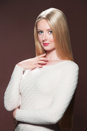 Pretty young blonde woman with beautiful hair on brown background Reklamní fotografie - 74887289