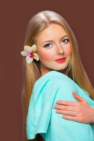 Pretty young blonde woman with beautiful hair, blue towel and flower orchid on brown background