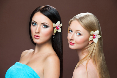 Portrait of beautiful white caucasian blonde and brunette woman with flower orchid