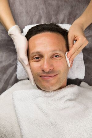 Male face, hands of professional beautician with gloves and white cotton sponges