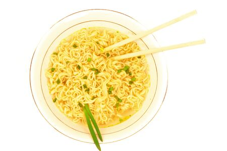 Top view of plate of fastfood soup with green onion, chopsticks and raw ramen instant noodle uncooked isolated on white background