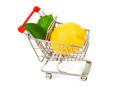 Lemon with green leaves in metal trolley isolated on white background Imagens